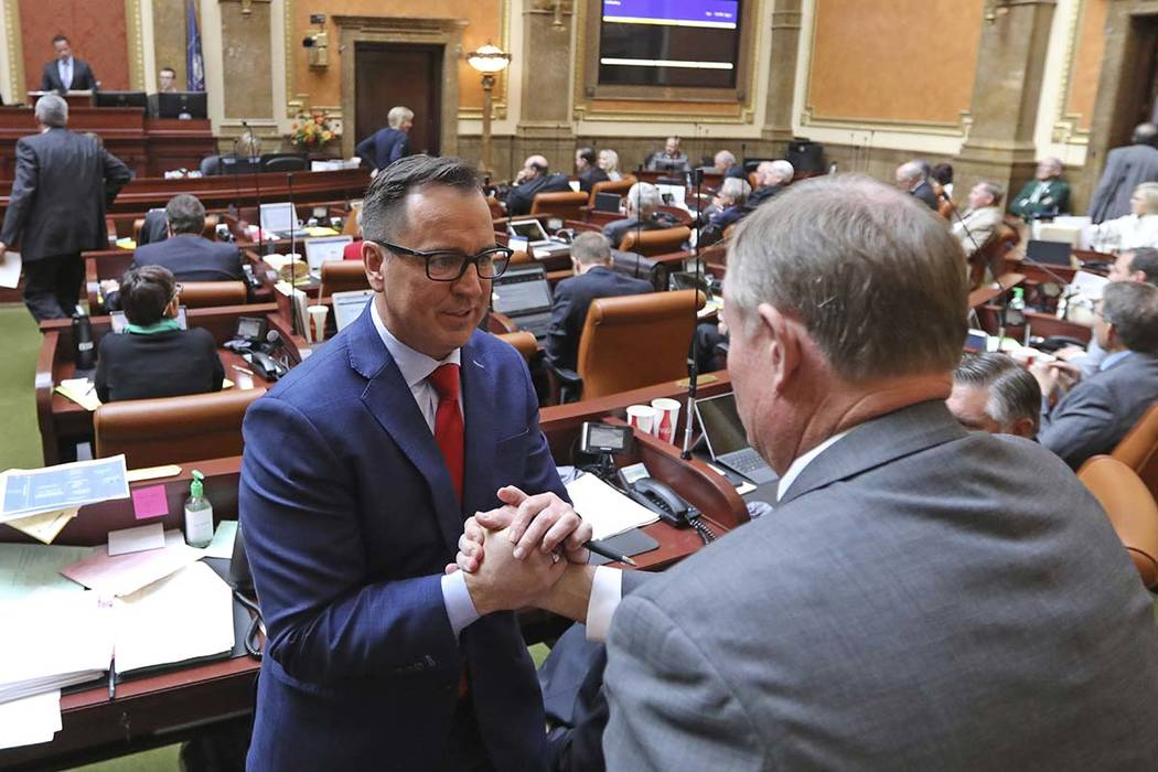 Republican outgoing House Speaker Greg Hughes, left, receives a handshake from Republican Sen. Evan Vickers after the Utah House of Representatives passed a compromise plan to legalize medical mar ...