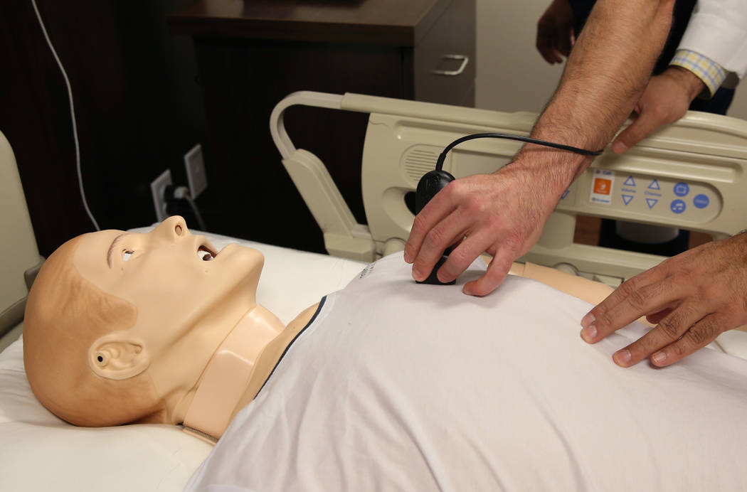 Matt Cadelago, left, emergency medicine resident at MountainView Hospital, demonstrates how an ultrasound is performed on SimMan 3G, an advance patient simulator, at MountainView Hospital as Dr. A ...