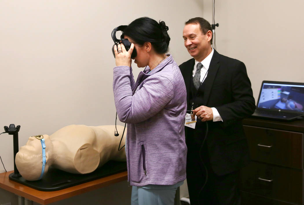 Kim Adams, surgical service educator, wearing virtual reality goggles, sees through SimMan's body at MountainView Hospital as Robert Turner, Simulation Center manager, looks on during the opening ...