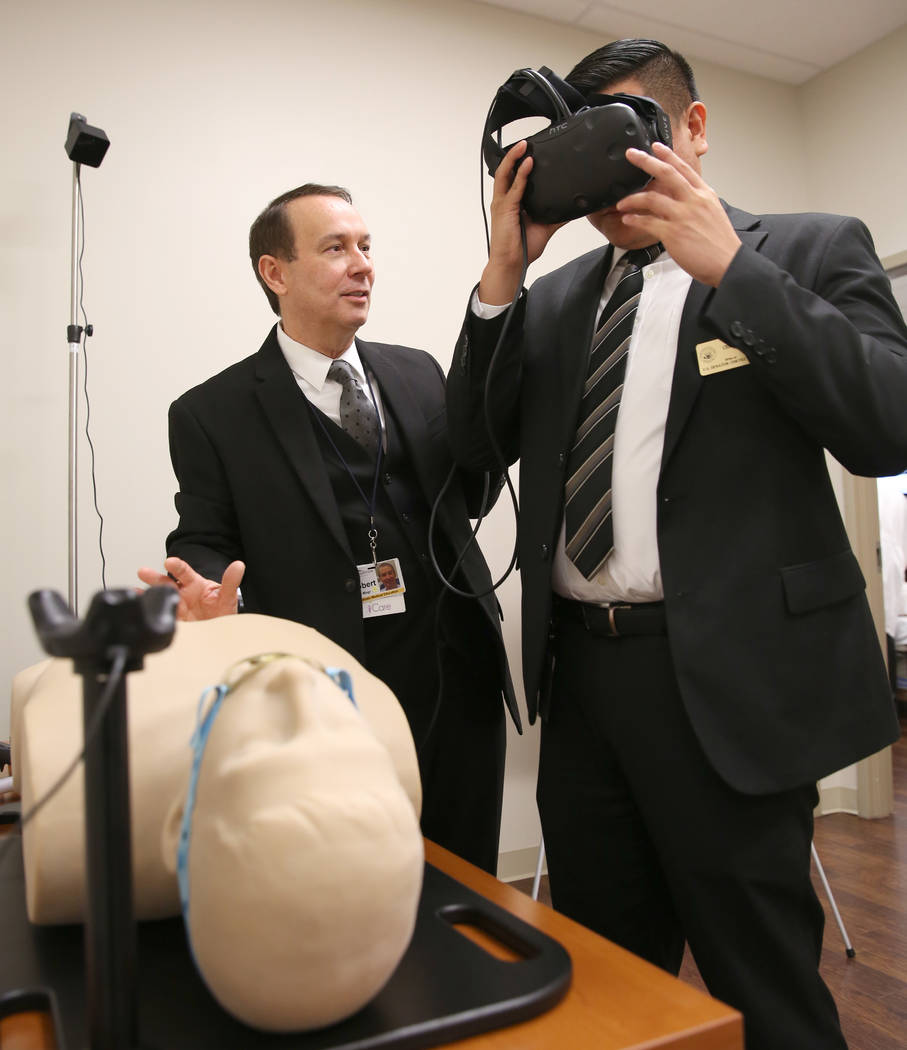Christian Bato, wearing virtual reality goggles, sees through SimMan's body at MountainView Hospital as Robert Turner, Simulation Center manager, looks on during the opening of the new Sunrise Hea ...