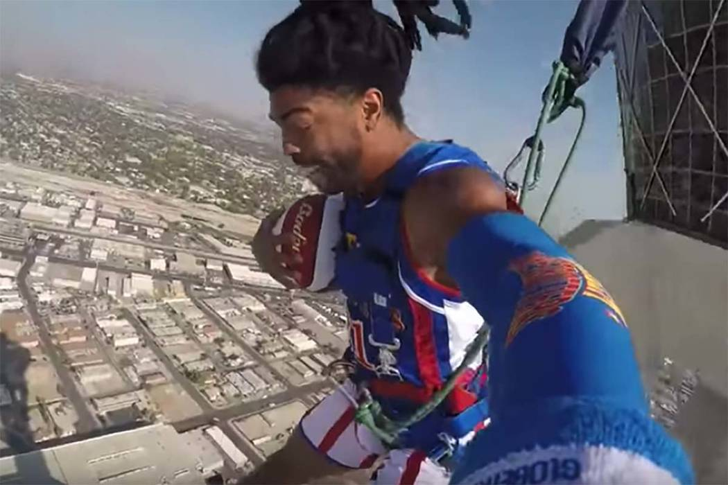 In a screen shot from video, Hammer Harrison of the Harlem Globetrotters uses SkyJump at the top of the Stratosphere in Las Vegas to perform the world's highest slam dunk. (YouTube)