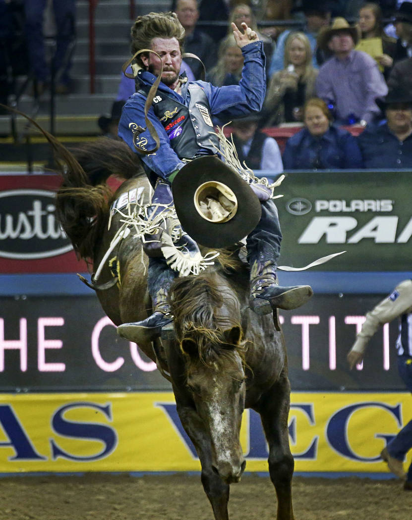 """Tilden Hooper of Carthage,Texas rides """"Redzilla"""" while competing in bareback riding during the opening night of the National Finals Rodeo at the Thomas & Mack Center in Las Vegas on ..."""