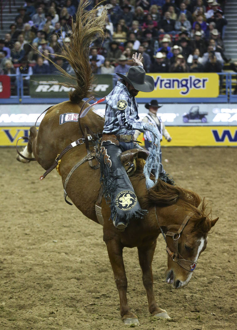 """Wade Sundell of Boxholm, Iowa rides """"Lock & Load"""" while competing in saddle bronc riding during the opening night of the National Finals Rodeo at the Thomas & Mack Center in Las ..."""
