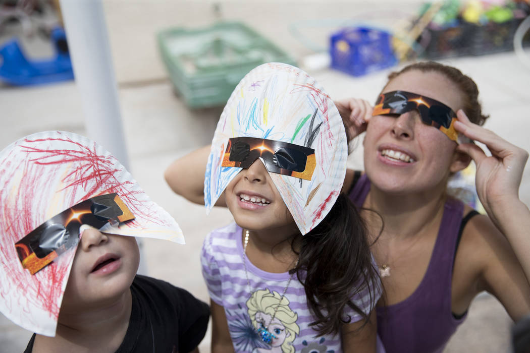 Joseph Hernandez-Bernabei, 3, from left, Gisele Oseguera, 3, and her mother Monica Cuevas, watch the solar eclipse at the Keeping Youth Educated daycare in Las Vegas, on Monday, Aug. 21, 2017. Eri ...