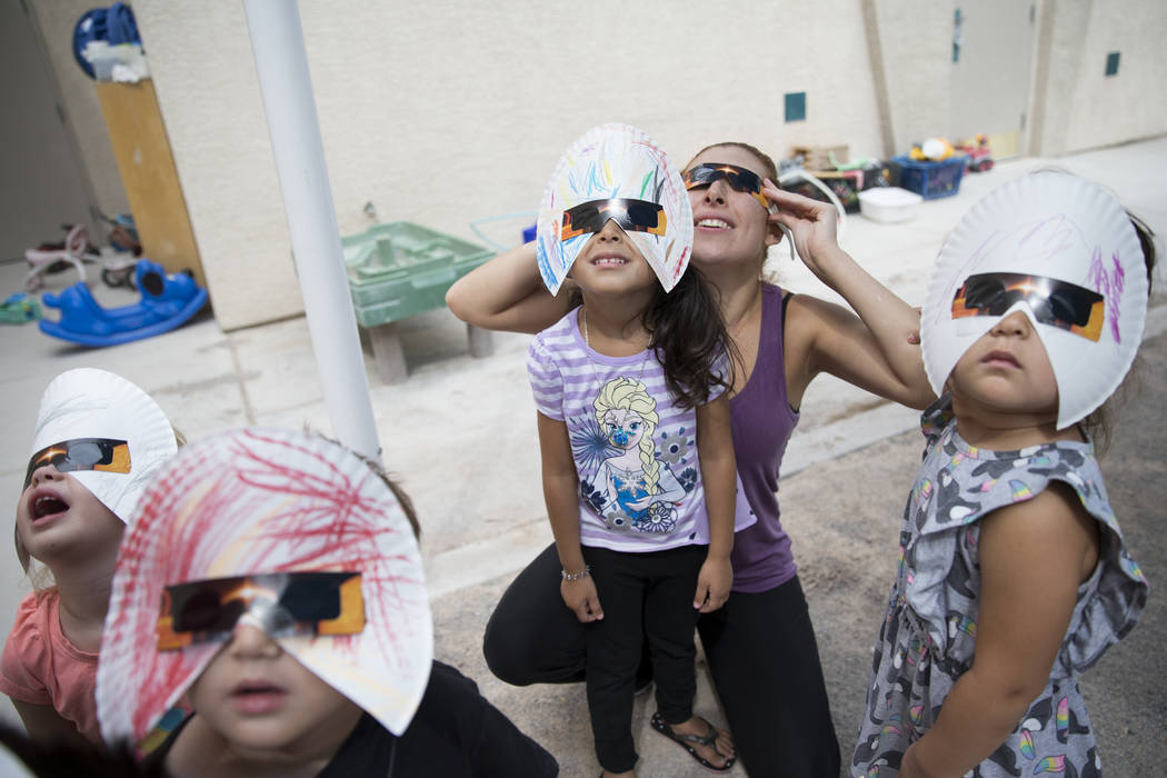 Amilya Durnen, 3, from left, Joseph Hernandez-Bernabei, 3, with his twin sister Sofia, far right, and Monica Cuevas with her daughter Gisele Oseguera, 3, watch the solar eclipse at the Keeping You ...