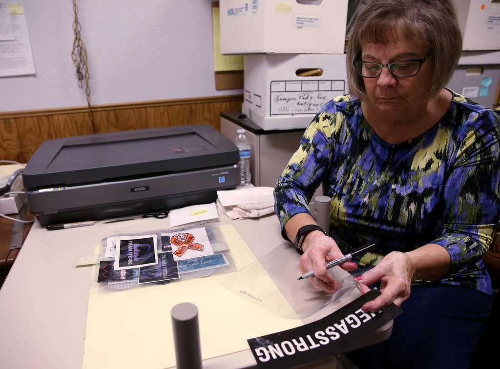 Clark County Museum volunteer Ilene Bernal rehouses and labels one of the final items Thursday, Dec. 6 2018, of the more than 17,000 items left at the makeshift memorial near the Las Vegas sign af ...