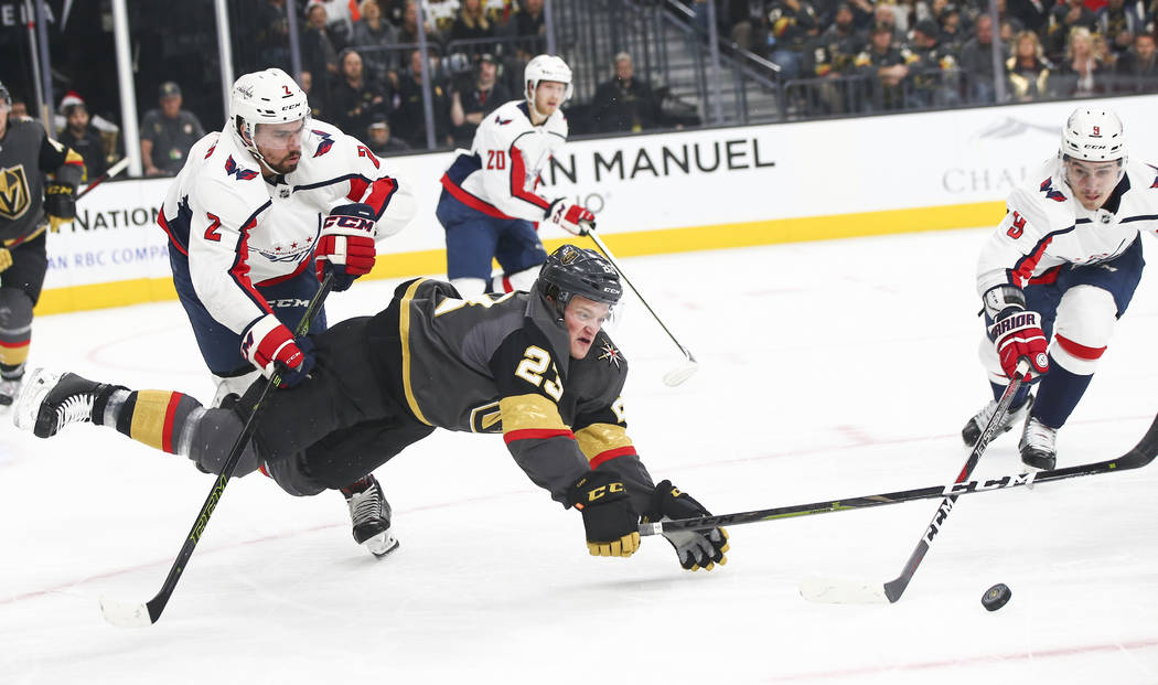 Golden Knights left wing Daniel Carr (23) gets pushed to the ice by Washington Capitals defenseman Matt Niskanen (2) while battling for the puck against Washington Capitals defenseman Dmitry Orlov ...