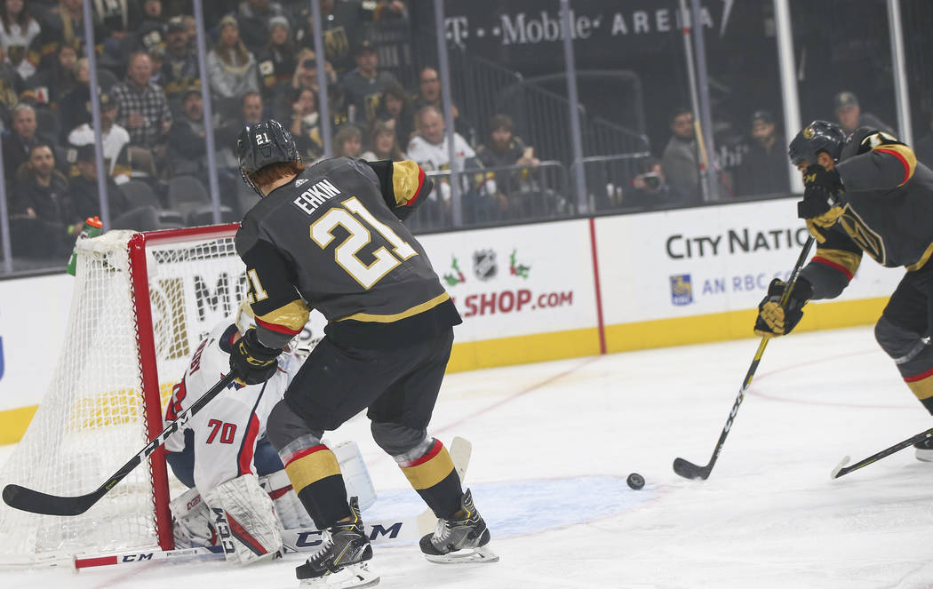 Golden Knights center Cody Eakin (21) passes the puck to Golden Knights right wing Ryan Reaves (75) who shoots to score a goal past Washington Capitals goaltender Braden Holtby (70) during the fir ...