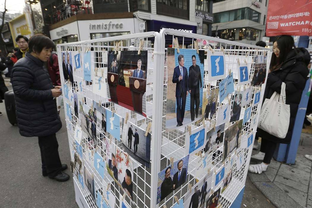 In this Nov. 25, 2018, file photo, photos of South Korean President Moon Jae-in and North Korean leader Kim Jong Un and unification flags are displayed during a campaign to welcome Kim's possible ...