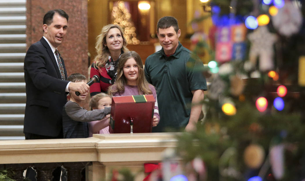 Wisconsin Gov. Scott Walker, left, with the help of the Mary and Don Miller family from Plainfield, Wis., flipped the switch to light the state Christmas Tree in the Capitol Rotunda, Tuesday, Dec. ...