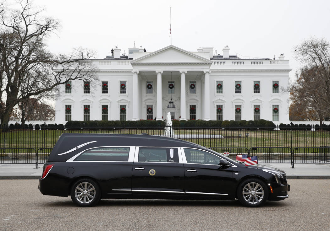 The hearse carrying the flag-draped casket of former President George H.W. Bush passes by the White House from the Capitol, heading to a State Funeral at the National Cathedral, Wednesday, Dec. 5, ...