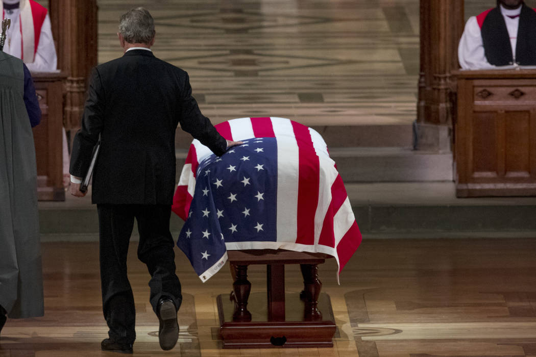 Former President George Bush touches the flag-draped casket of his father, former President George H.W. Bush, as he prepares to speak during his State Funeral at the National Cathedral, Wednesday, ...