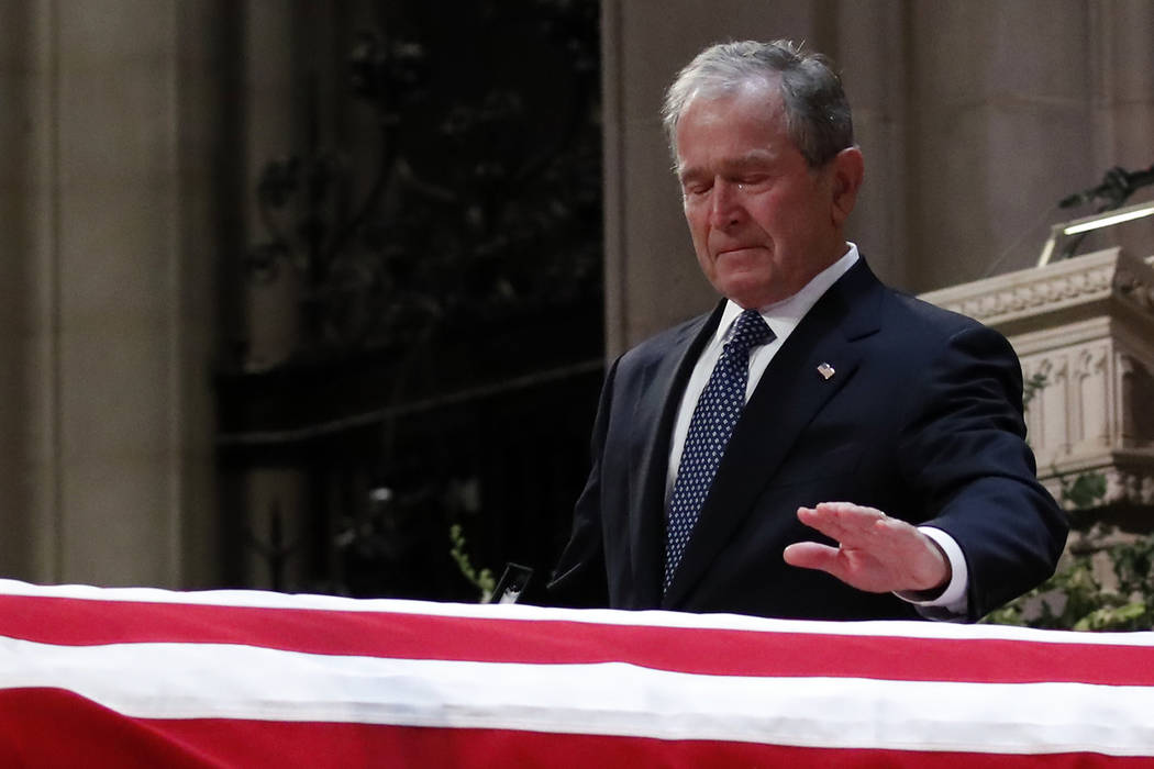 Former President George W. Bush touches the casket of his father, former President George H.W. Bush, at the State Funeral at the National Cathedral, Wednesday, Dec. 5, 2018, in Washington.(AP Phot ...