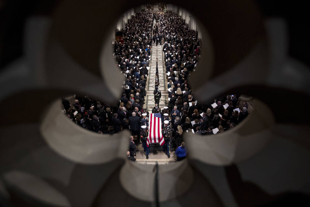 The flag-draped casket of former President George H.W. Bush is carried out by a military honor guard during a State Funeral at the National Cathedral, Wednesday, Dec. 5, 2018, in Washington. (AP P ...