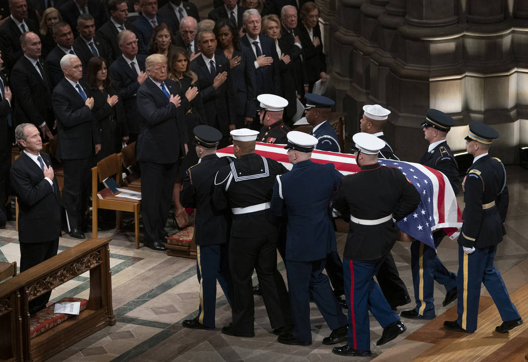 The flag-draped casket of former President George H.W. Bush is carried by a military honor guard past former President George W. Bush, President Donald Trump, first lady Melania Trump, former Pres ...