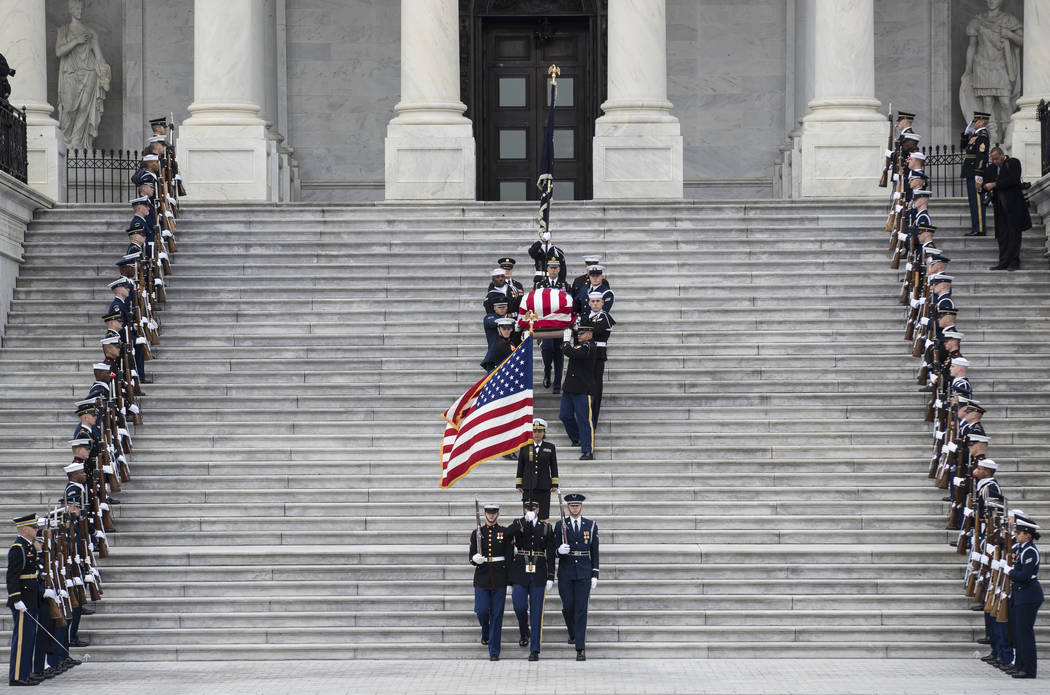 The flag-draped casket of former President George H.W. Bush is carried by a joint services military honor guard down the steps of the U.S. Capitol, Wednesday, Dec. 5, 2018, in Washington. (Sarah S ...