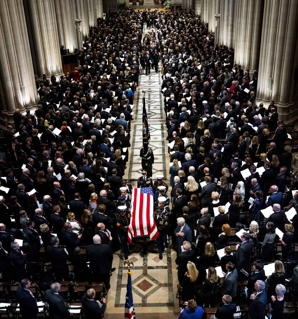 The flag-draped casket of former President George H.W. Bush is carried out by a military honor guard during a State Funeral at the National Cathedral, Wednesday, Dec. 5, 2018, in Washington. (Doug ...