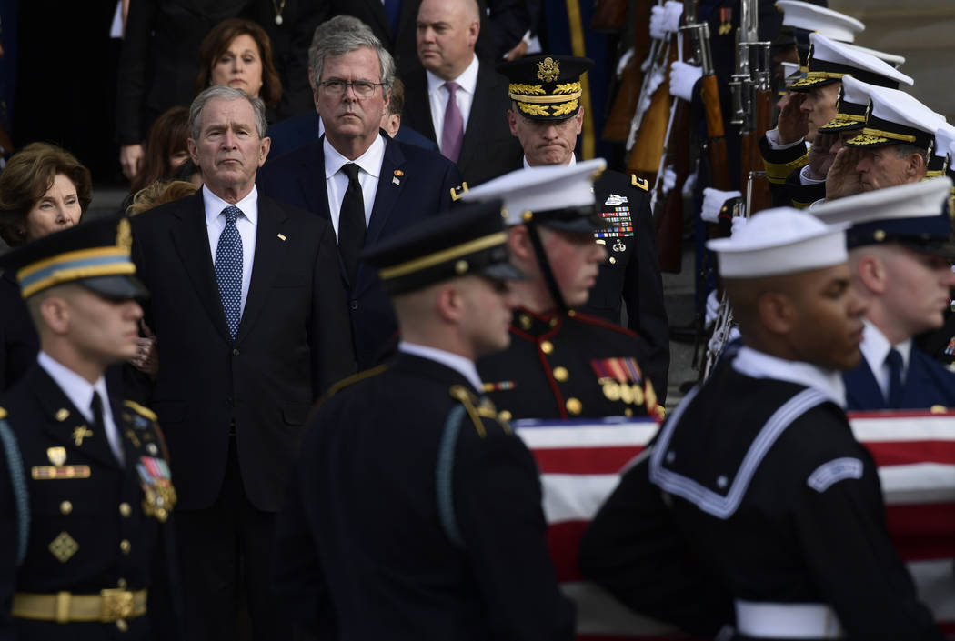 Former President George W. Bush, flanked by his wife Laura Bush, left, and brother former Florida Gov. Jeb Bush, watch as the casket of former President George H.W. Bush is carried out after a Sta ...