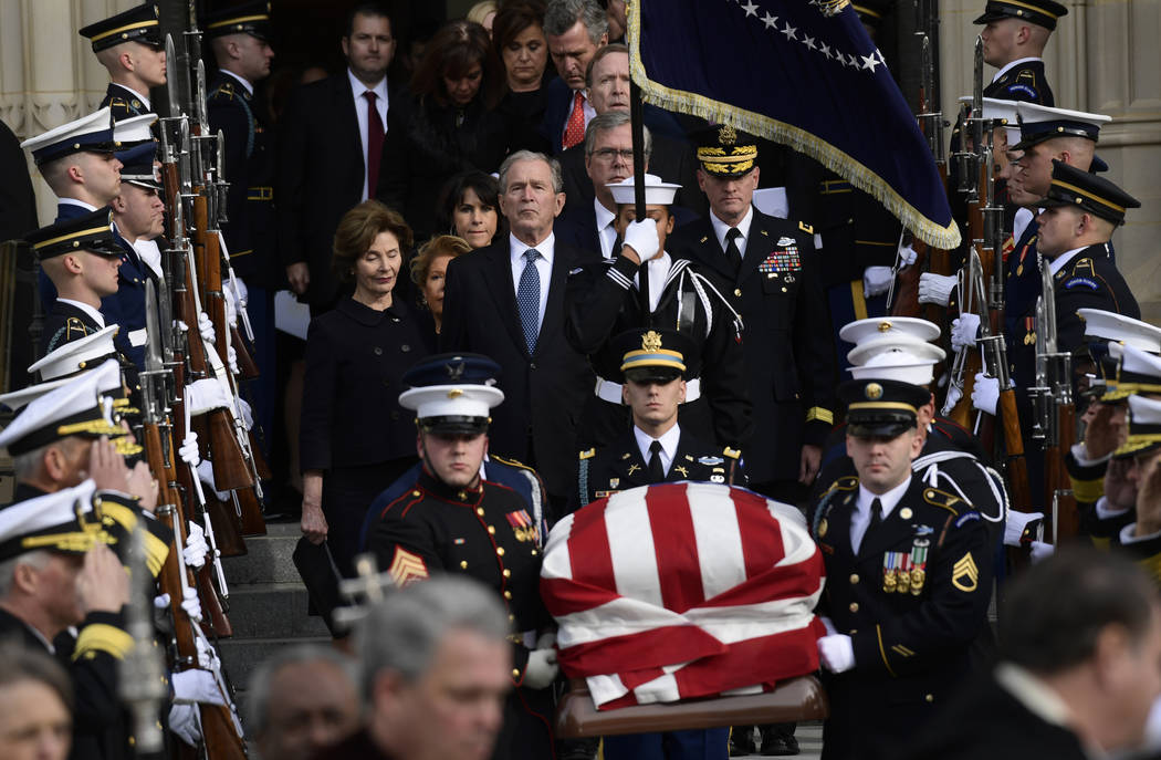 Former President George W. Bush and his wife Laura Bush, center, join their family as they follow the casket of former President George H.W. Bush as it is carried from the State Funeral at the Nat ...