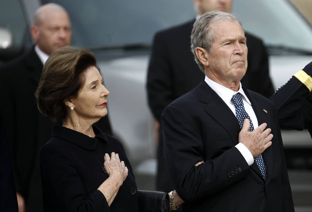 Former first lady Laura Bush, left, and former President George W. Bush watch as the flag-draped casket of former President George H.W. Bush arrives before a State Funeral at the National Cathedra ...