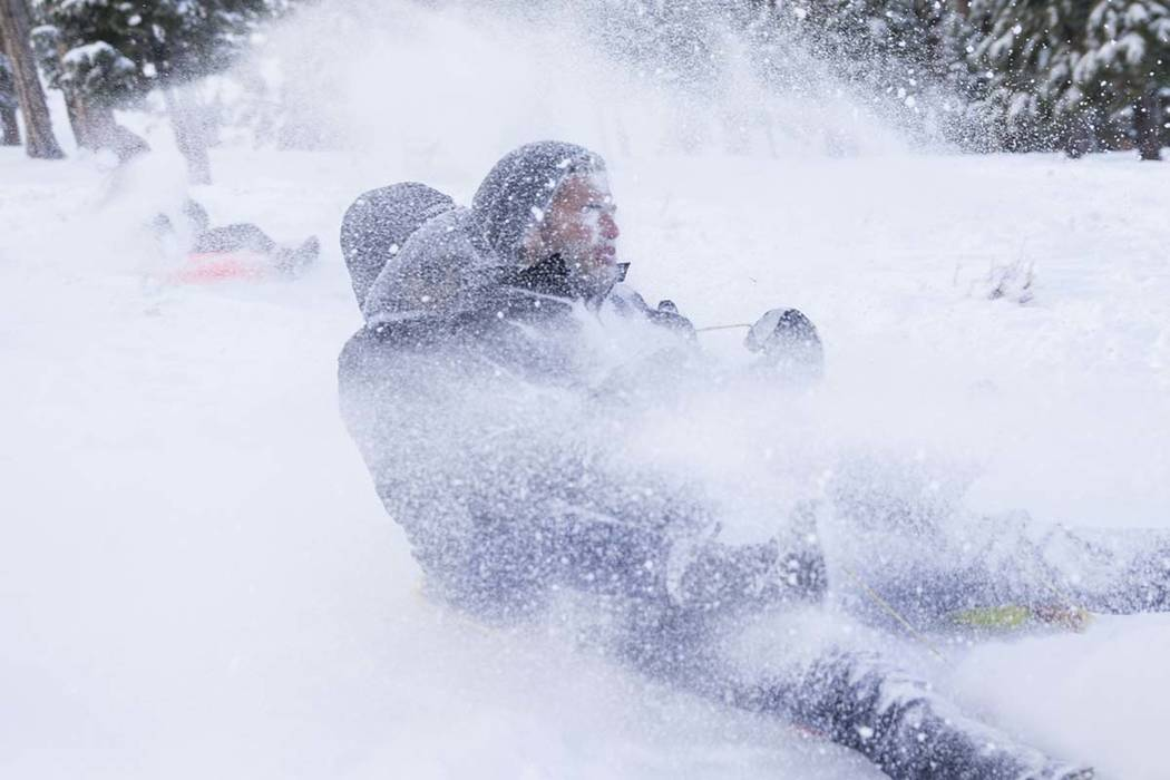 Dominic Marchese, right, and Ismara Escalona ride their sled through a wall of snow at Lee Meadows on Friday, Nov. 30, 2018, outside Lee Canyon near Las Vegas. (Benjamin Hager/Las Vegas Review-Jou ...