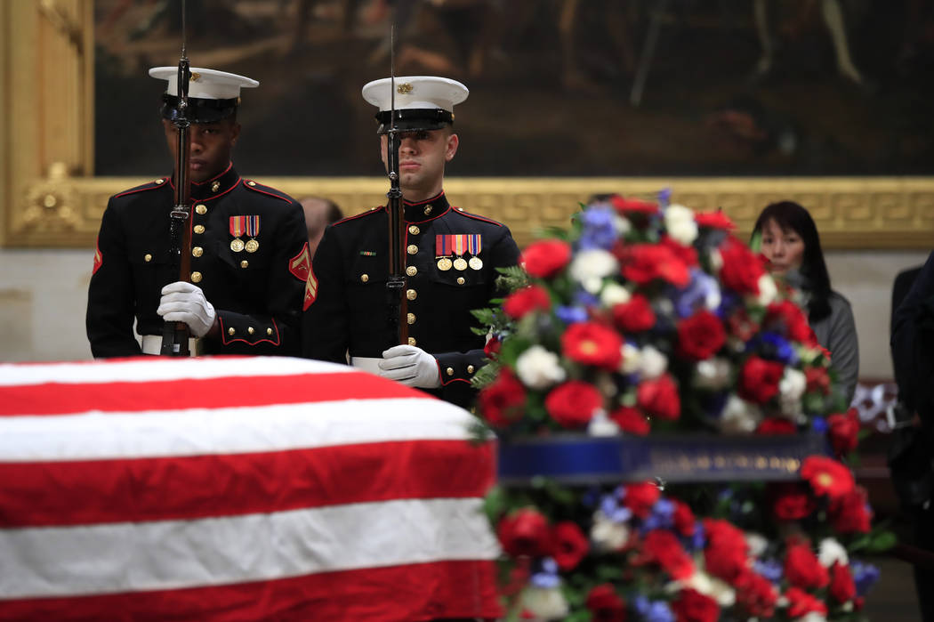 U.S. Marine Corps honor guard execute a rifle salute during the changing of the guard at the Capitol Rotunda where former President George H.W. Bush lies in state Wednesday, Dec. 5, 2018. (AP Phot ...