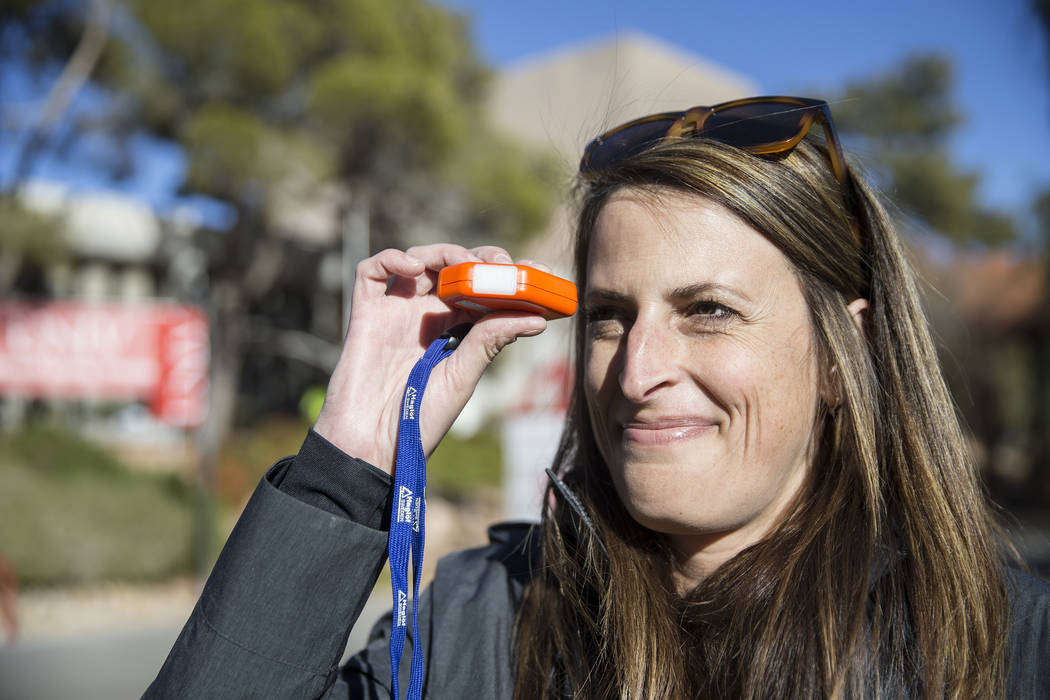 Andi Porreca, with the Nevada Division of Forestry, uses a a clinometer to measure the height of a Chinese Flame Tree on Thursday, Dec. 13, 2018, at UNLV, in Las Vegas. Benjamin Hager Las Vegas Re ...