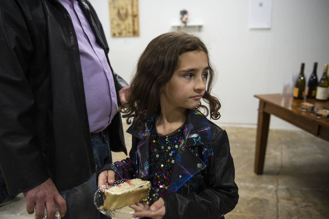 Beatrix Wiersma, 8, from Las Vegas takes a piece of cake being served at an exhibit at Core Contemporary Gallery in Las Vegas, Thursday, Dec. 6, 2018. Caroline Brehman/Las Vegas Review-Journal