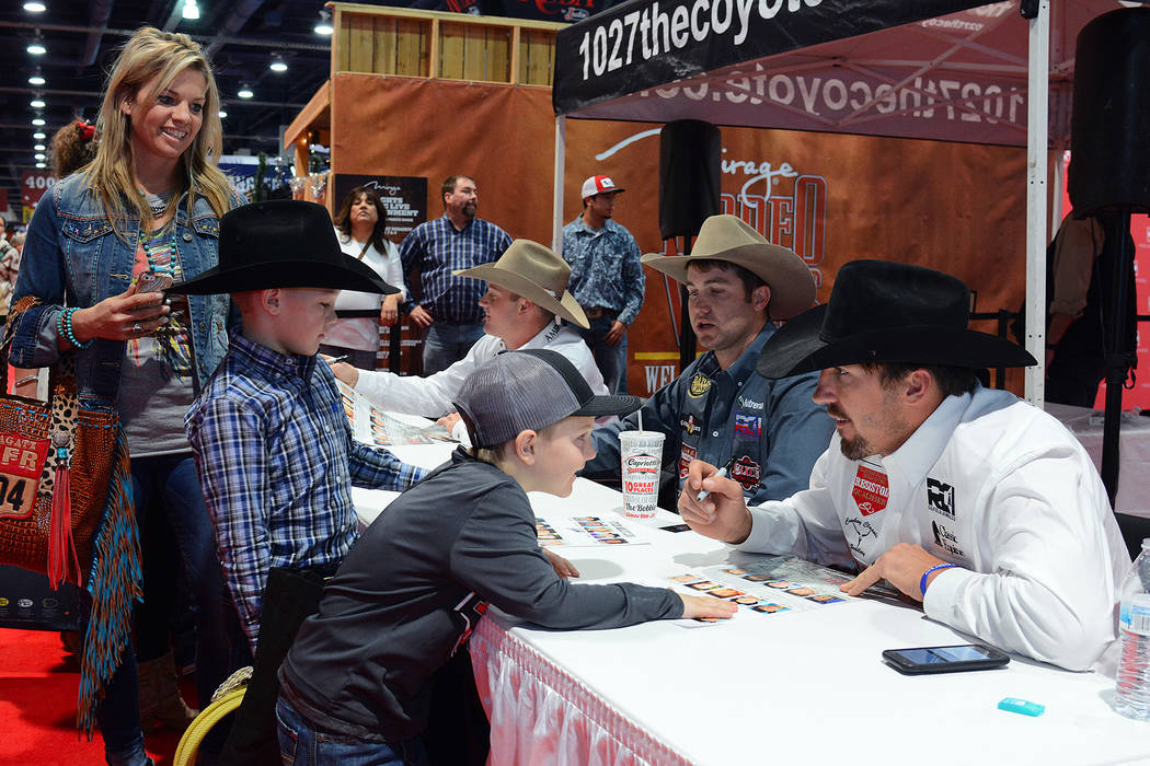 Steer Wrestler Tyler Pearson engages with a young fan at an autograph session at Cowboy Christmas during the 2017 Wrangler National Finals Rodeo. Photo by Steve Spatafore/Special to the Review-Journal