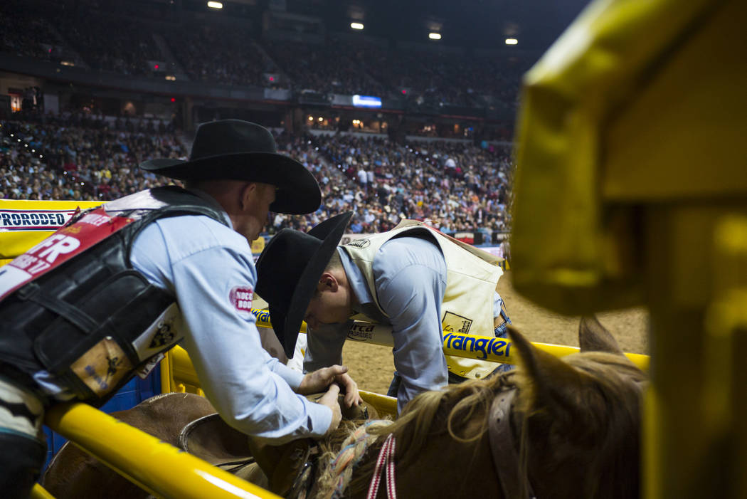 Jacobs Crawley, left, prepares before competing in the saddle bronc riding event during the second night of the National Finals Rodeo at the Thomas & Mack Center in Las Vegas on Friday, Dec. 8 ...