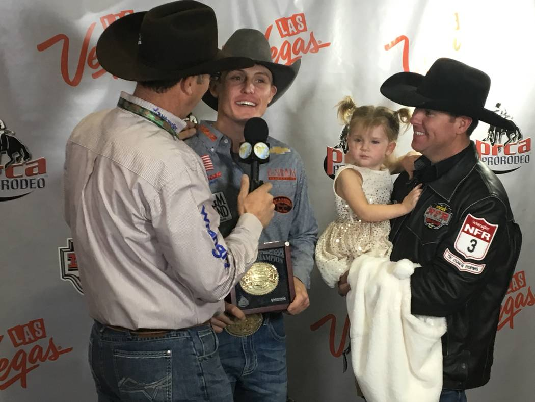 Tuf Cooper, second from left, clutches the gold buckle earned for winning the title of all-around world champion cowboy at the 2017 Wrangler National Finals Rodeo, as brother-in-law and 13-time al ...