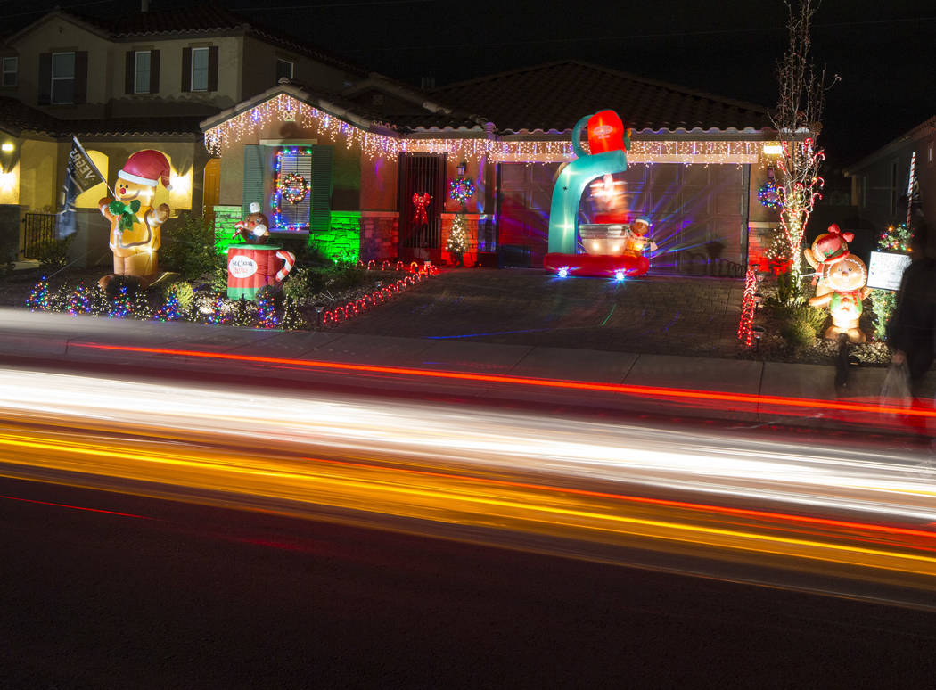 A car passes the house of Becky and GG Misa decorated with a Christmas light display that is synchronized to the entrance music for the Golden Knights located at 730 Bollons Island St. in Henderso ...