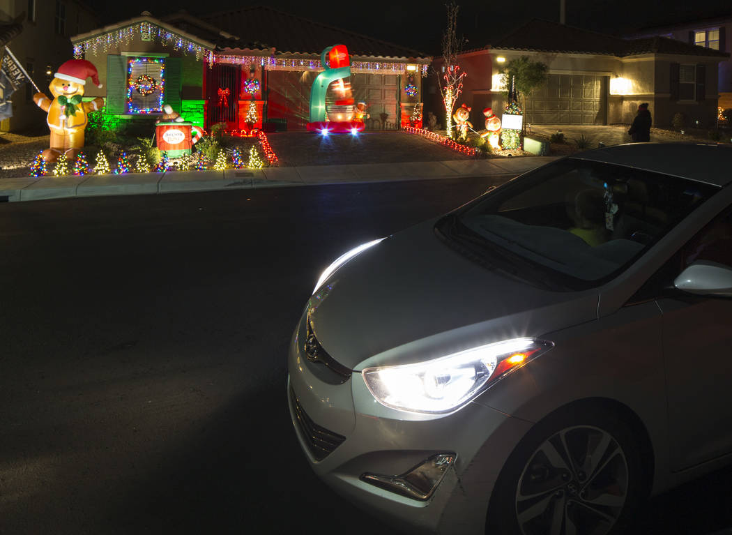 A family in a car watches Becky and GG Misa's Christmas light display that is synchronized to the entrance music for the Golden Knights located at 730 Bollons Island St. in Henderson on Wednesday, ...