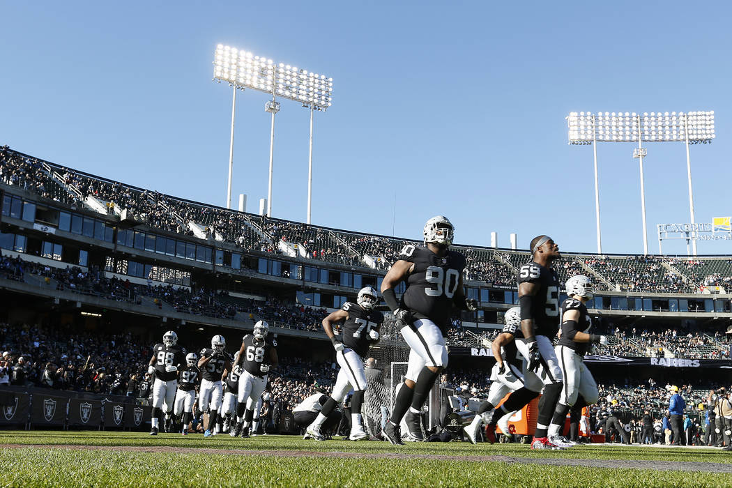 Oakland Raiders players run onto the field before an NFL football game against the Kansas City Chiefs in Oakland, Calif., Sunday, Dec. 2, 2018. (AP Photo/D. Ross Cameron)