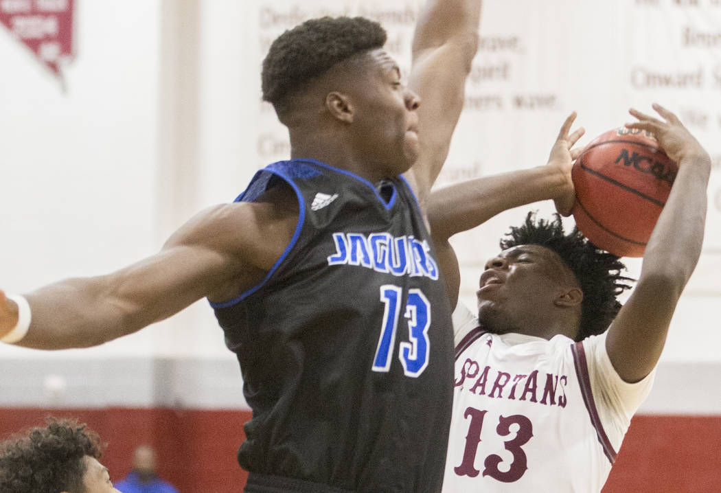 Cimarron-Memorial senior Brian Lang (13) collides with Desert Pines junior Darnell Washington (13) on the way to the rim in the first quarter on Wednesday, Nov. 28, 2018, at Cimarron-Memorial Hig ...
