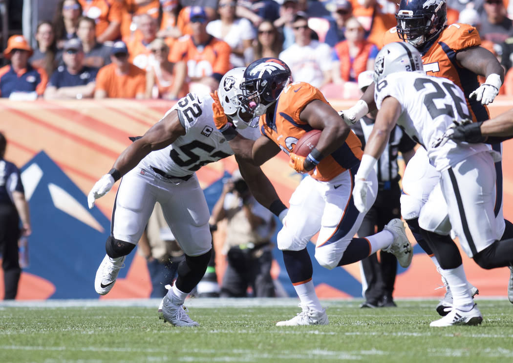 Denver Broncos running back C.J. Anderson (22) carries the football as Oakland Raiders defensive end Khalil Mack (52) comes in for a tackle in the first half of their game in Denver, Colo., Sunday ...