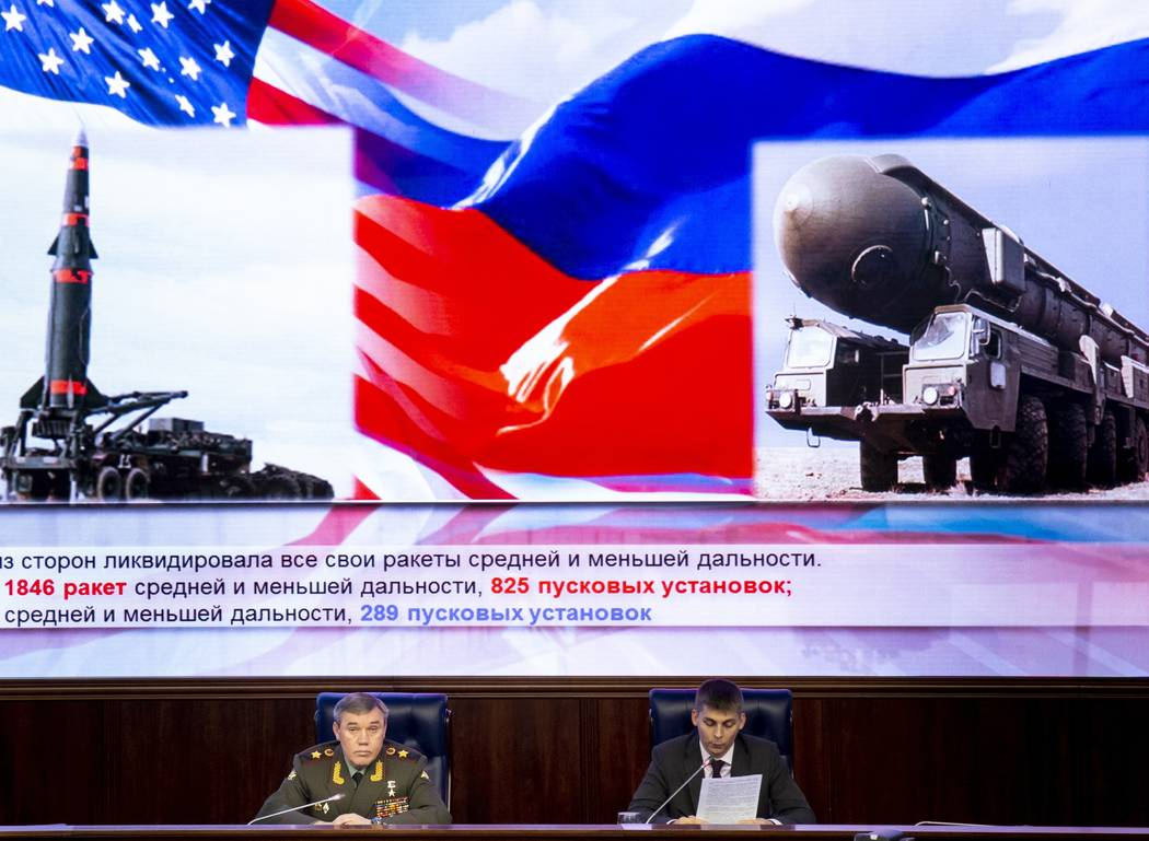 Deputy Chief of General Staff of Russia Valery Gerasimov, left, delivers his speech during a briefing in the Russian Defense Ministry's headquarters in Moscow, Russia, Wednesday, Dec. 5, 2018. Gen ...