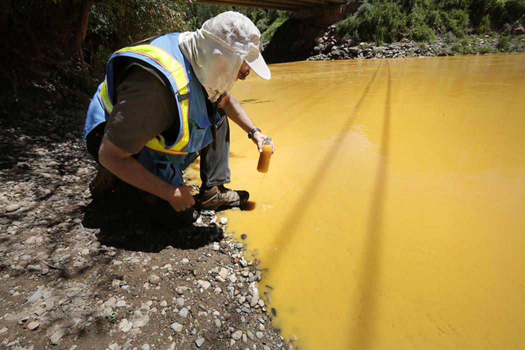 Dan Bender of the La Plata County Sheriff's Office takes a water sample on Aug. 6, 2015, from the Animas River near Durango, Colo., after the accidental release of an estimated 3 million gallons o ...