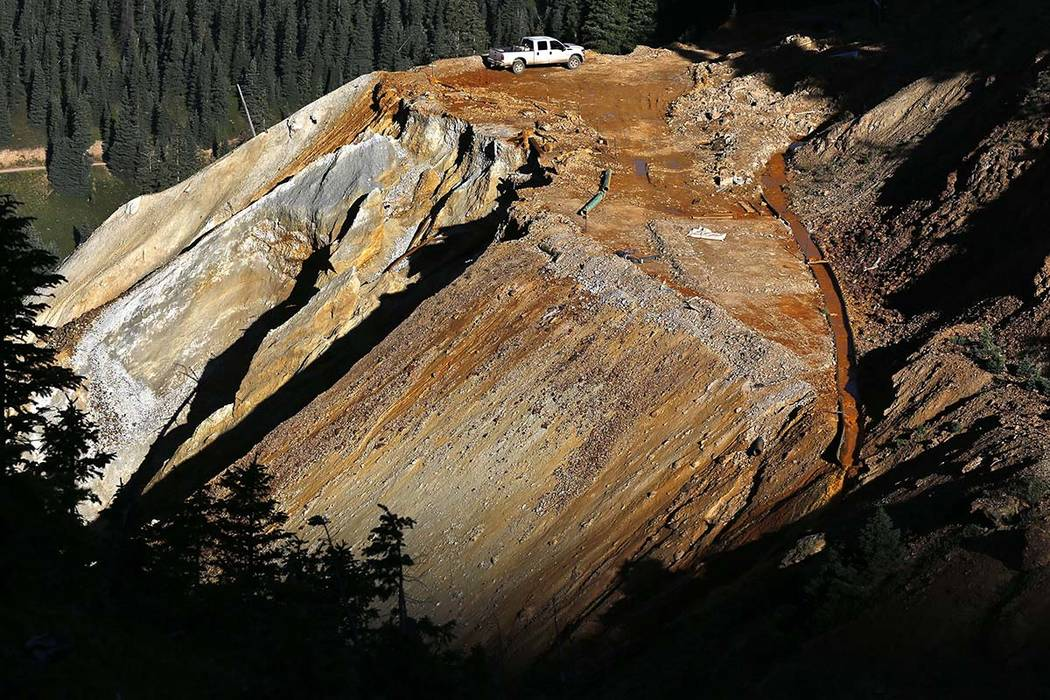 Wastewater flows on Aug. 13, 2015, down a trough, right, from the site of the blowout at the Gold King mine which triggered a major spill of toxic wastewater, outside Silverton, Colo. Crumbling mi ...