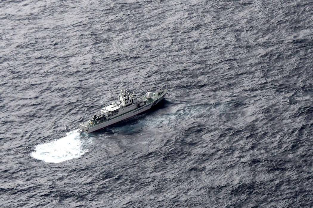 In this aerial photo, Japan's Coast Guard ship is seen at sea during a search operation for U.S. Marine refueling plane and fighter jet off Muroto, Kochi prefecture, southwestern Japan, Thursday, ...