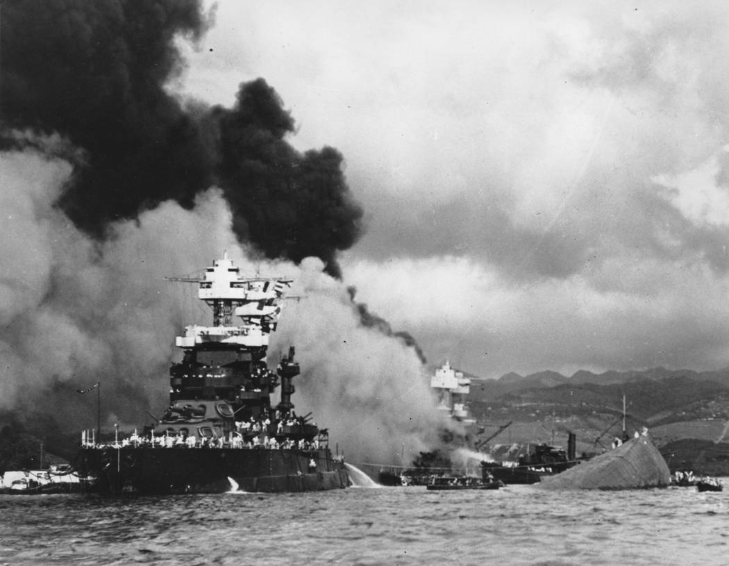 FILE - In this Dec. 7, 1941 file photo, part of the hull of the capsized USS Oklahoma is seen at right as the battleship USS West Virginia, center, begins to sink after suffering heavy damage, whi ...