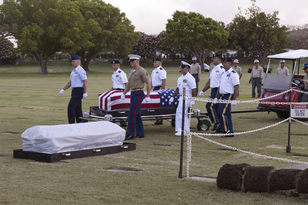 FILE - In this July 27, 2015 file photo, military pallbearers escort the exhumed remains of unidentified crew members of the USS Oklahoma killed in the 1941 bombing of Pearl Harbor that were disin ...