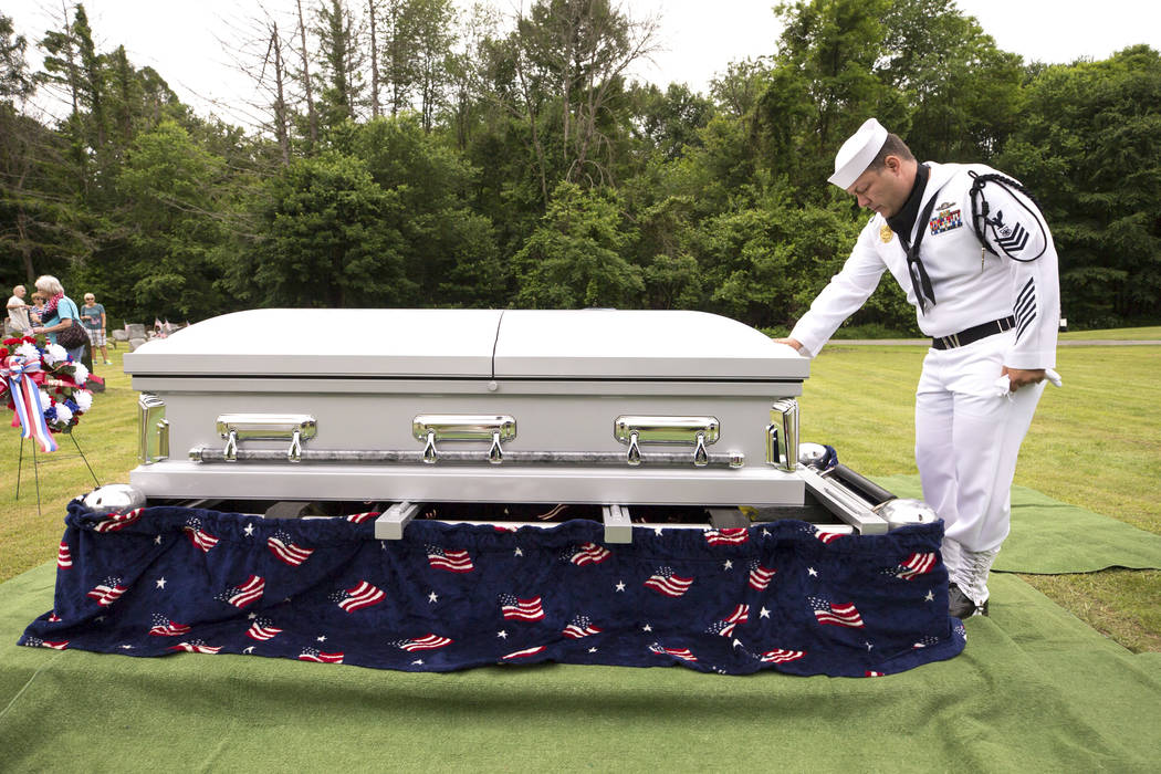 In this June 9, 2018, file photo, U.S. Navy Master at Arms First Class Robert Linke, a Los Angeles native stationed at Naval Weapons Station Earle in Colts Neck, N.J., pauses at the casket of U.S. ...