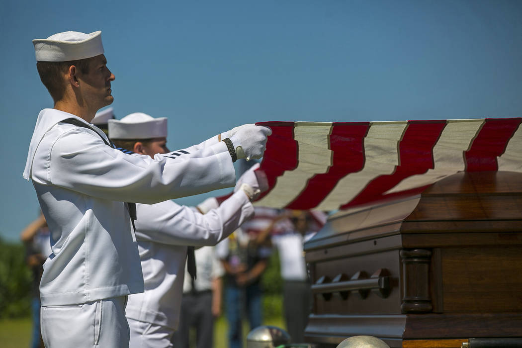 FILE - In this July 7, 2018 file photo, U.S. Navy sailors fold the U.S. flag draped over the casket with the remains of Seaman First Class Leon Arickx at Sacred Heart Cemetery in Osage, Iowa. Aric ...