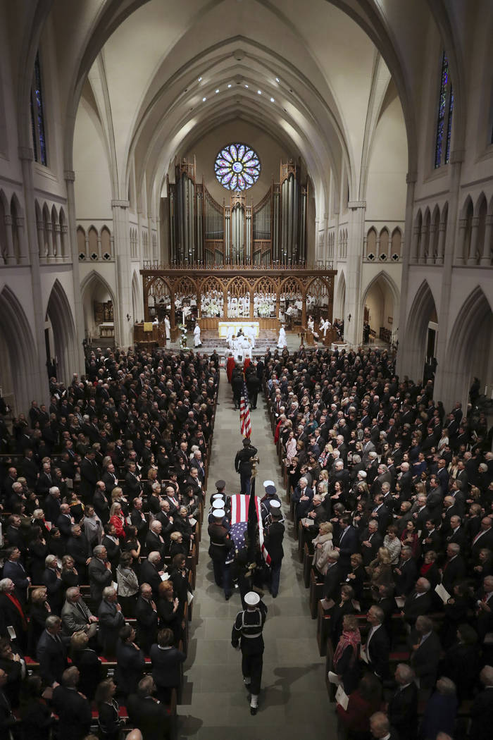 The flag-draped casket of former President George H.W. Bush is carried by a joint services military honor guard into St. Martin's Episcopal Church during a funeral for former President George H.W. ...