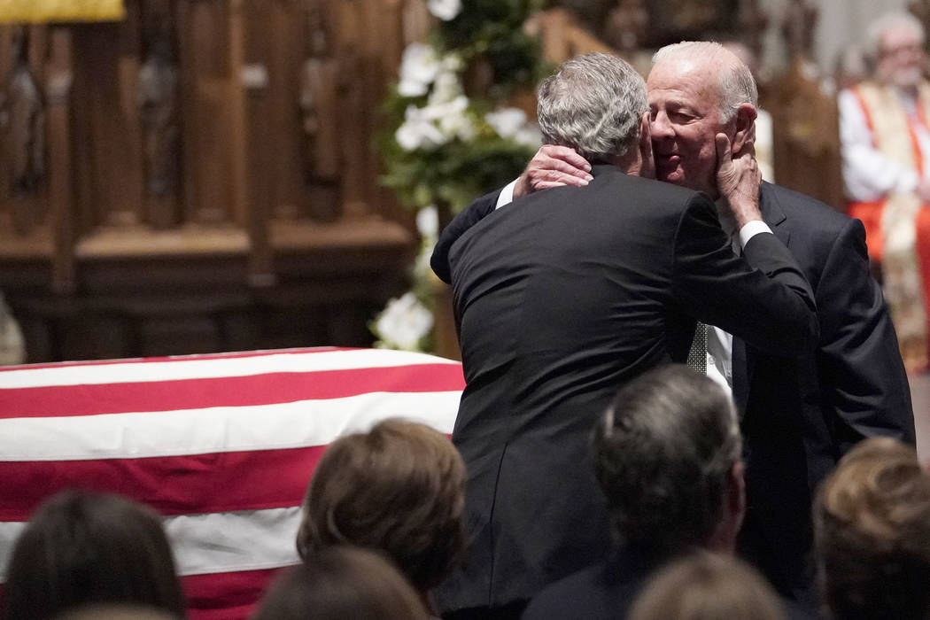 Former President George W. Bush embraces former Secretary of State James Baker, right, after he gave a eulogy during the funeral for former President George H.W. Bush at St. Martin's Episcopal Chu ...