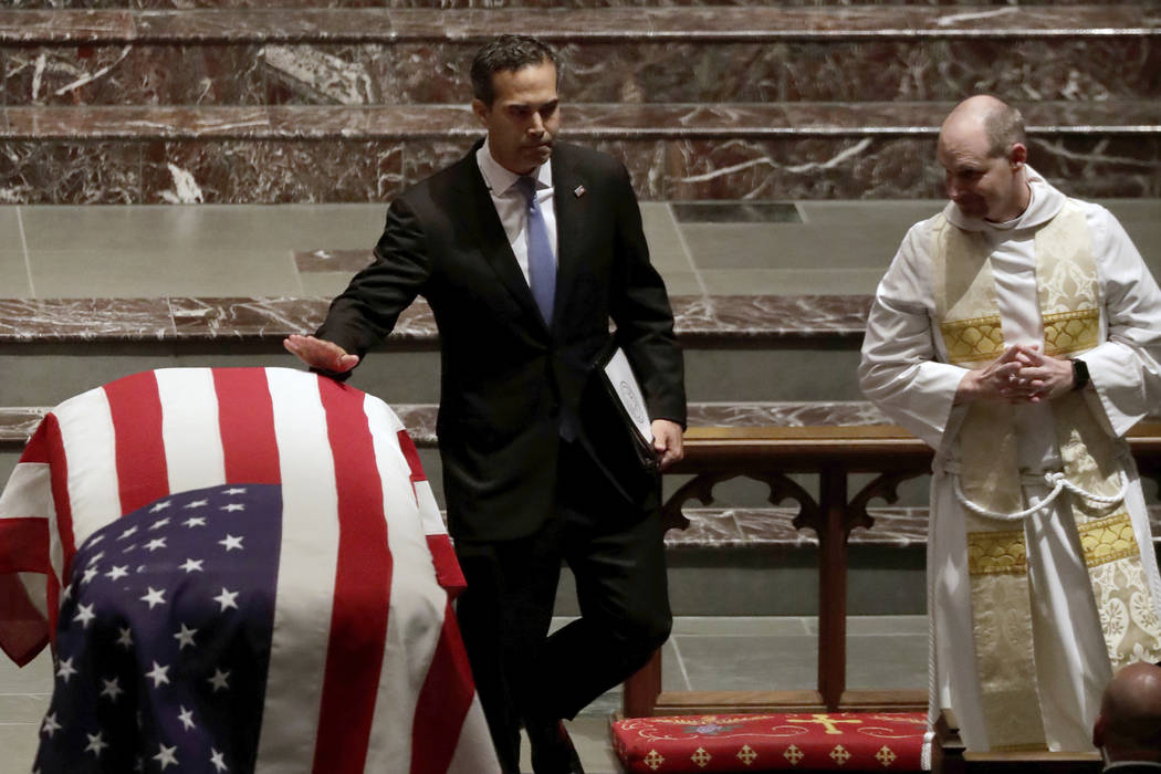George P. Bush touches the flag-draped casket after giving a eulogy during a funeral for former President George H.W. Bush at St. Martin's Episcopal Church Thursday, Dec. 6, 2018, in Houston. (AP ...