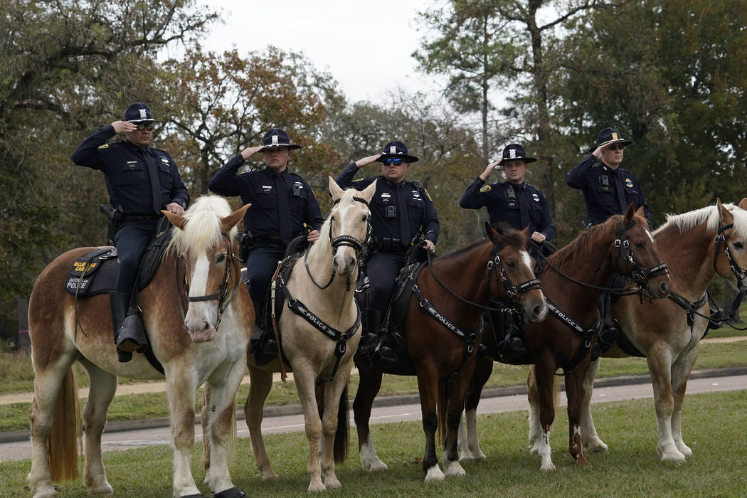 Police on horseback salute as the hearse carrying the flag-draped casket of former President George H.W. Bush heads to the Union Pacific train facility Thursday, Dec. 6, 2018, in Houston. (AP Phot ...