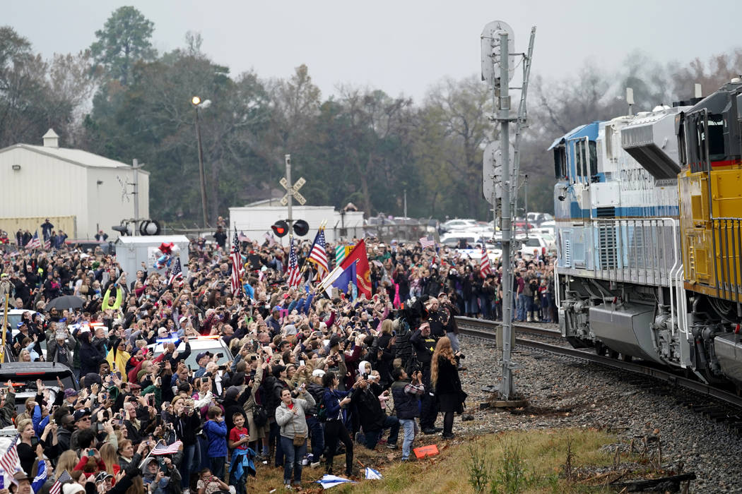 People pay their respects as the train carrying the casket of former President George H.W. Bush passes Thursday, Dec. 6, 2018, along the route from Spring to College Station, Texas. (AP Photo/Davi ...