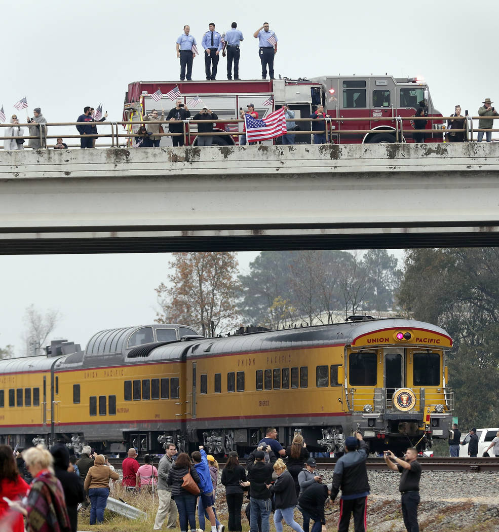 Firefighters stand on their truck and salute along with other attendants on an overpass as the train carrying the body of former president George H.W. Bush travels past on the way to Bush's final ...